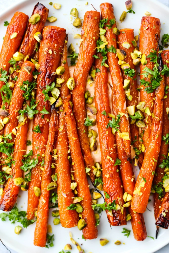 maple-roasted carrots over harissa yogurt sauce with chopped pistachios, parsley, and lemon zest