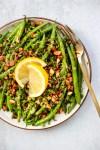 garlic sauteed green beans with dijon vinaigrette, toasted almonds, lemon wedges on plate