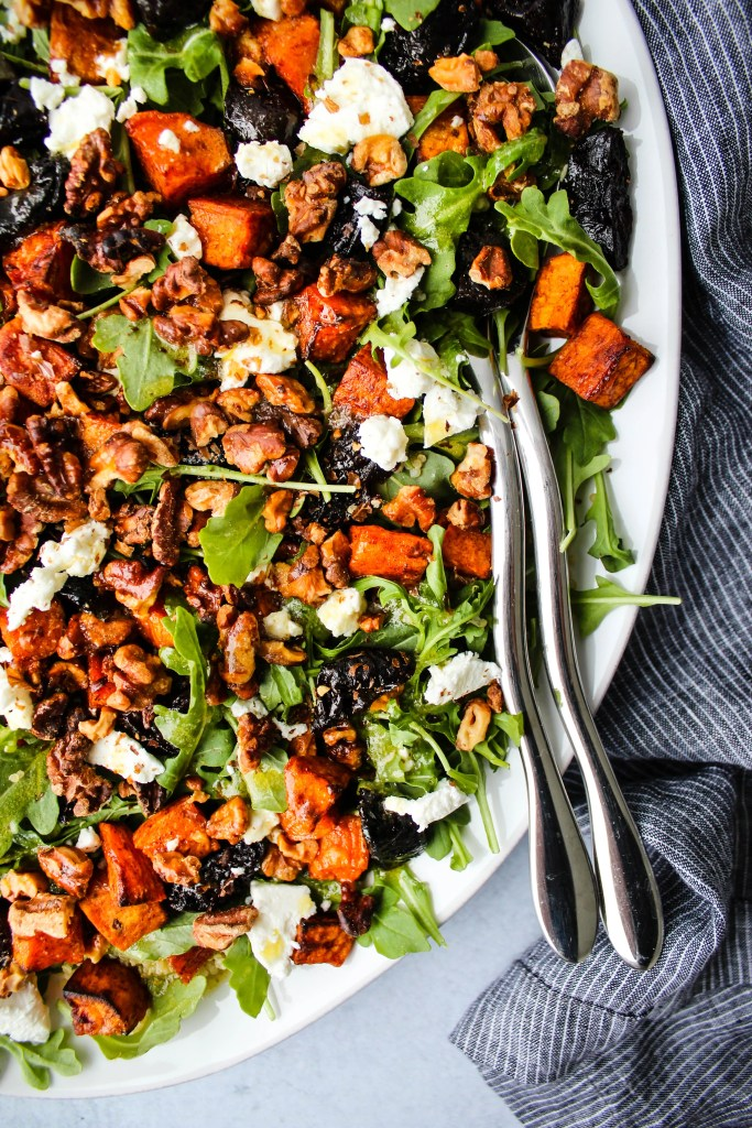 warm prune salad on white plate with arugula, sweet potatoes, goat cheese, and toasted walnuts