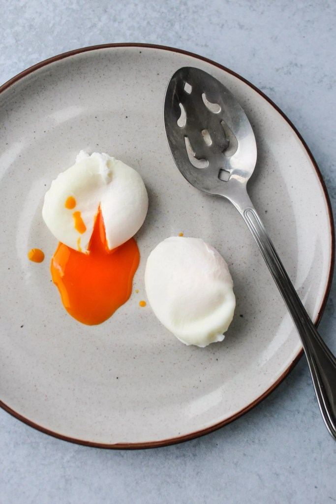 poached eggs with runny yolk on plate with slotted spoon