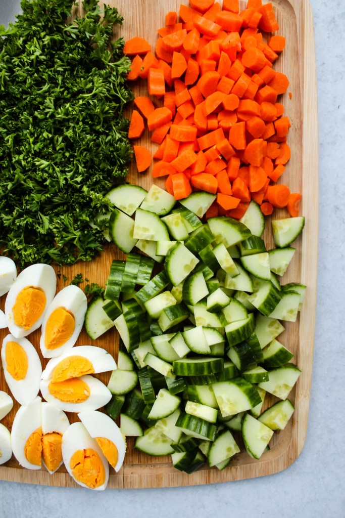 chopped parsley, carrots, cucumber, and hard boiled eggs on a wooden board