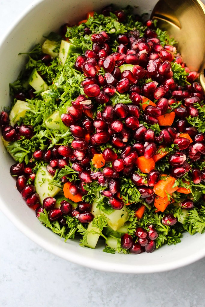 quinoa salad with chopped cucumber, carrots, parsley, pomegranates in while bowl