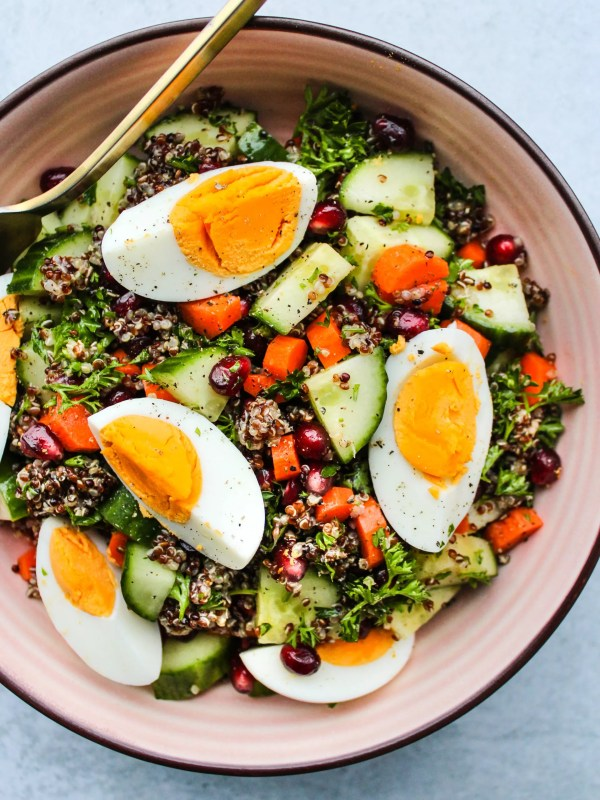 chopped quinoa salad with cucumbers, carrots, parsley, pomegranates, hard boiled eggs in pink bowl