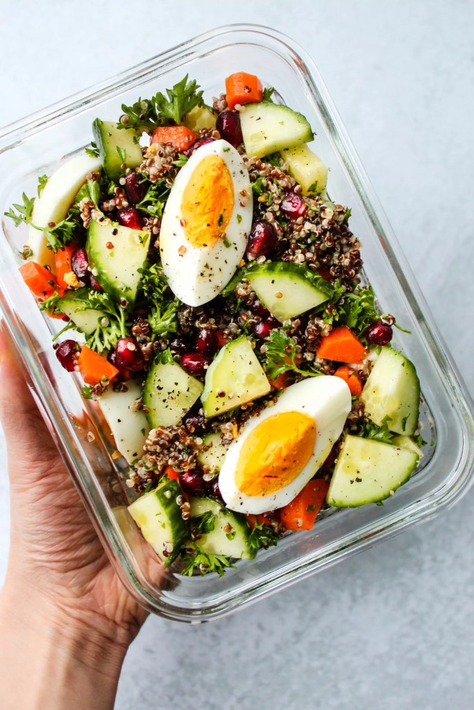chopped quinoa salad with cucumbers, carrots, parsley, pomegranates, hard boiled eggs in meal prep container