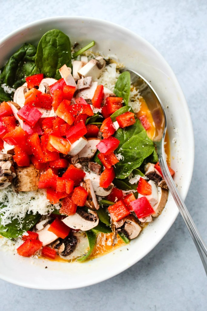 whisked eggs with chopped red peppers, mushrooms, spinach, and gruyere in white bowl