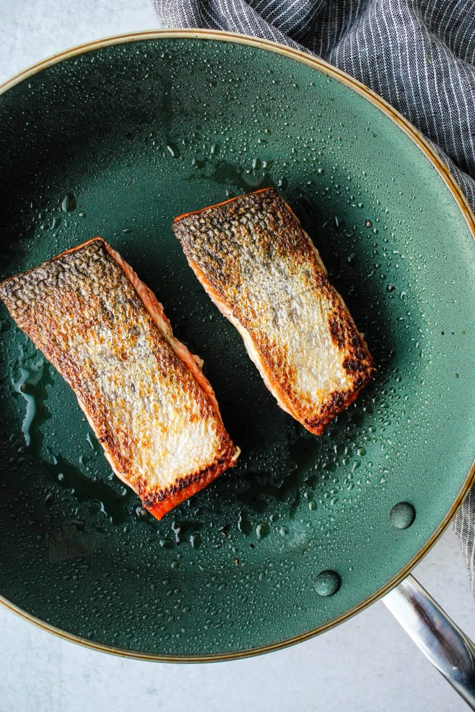 two crispy salmon fillets with skin on frying pan