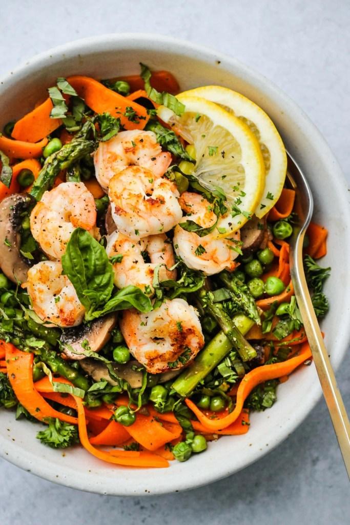 white bowl with sweet potato fettuccine noodles, asparagus, peas, shrimp, lemon