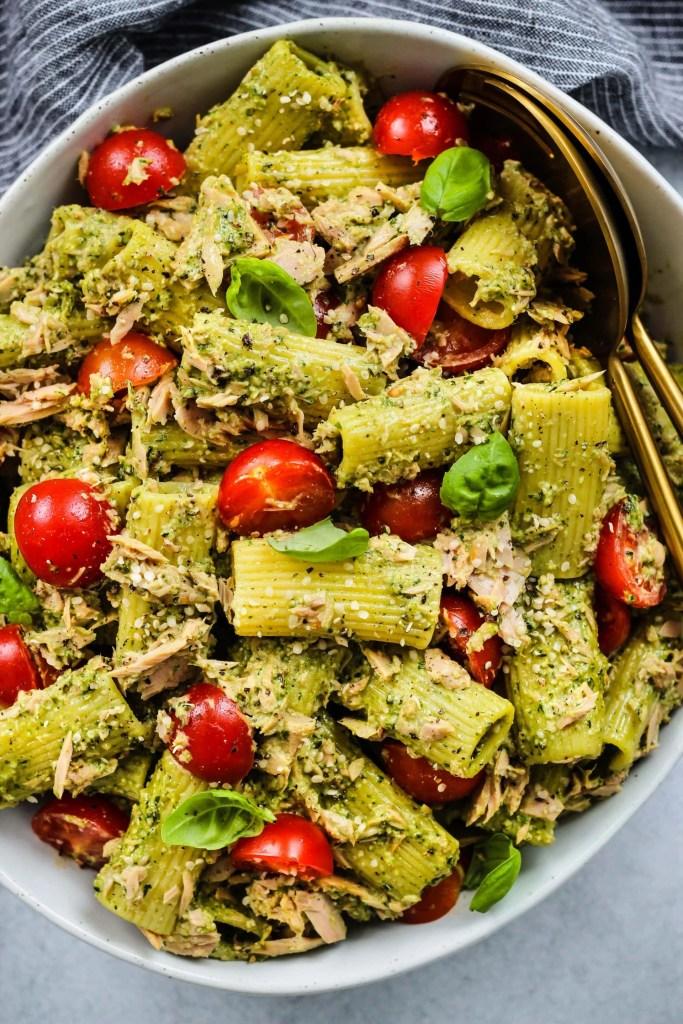 overhead shot of large white bowl with tuna pasta salad, pesto, cherry tomatoes