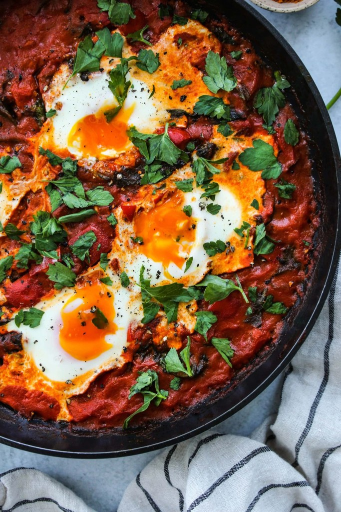 coconut curry shakshuka with runny yolks in a black skillet