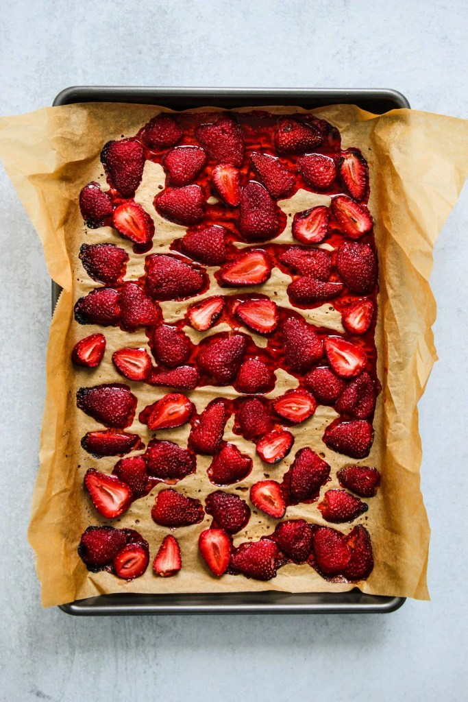 overhead shot of roasted strawberries on parchment lined baking sheet