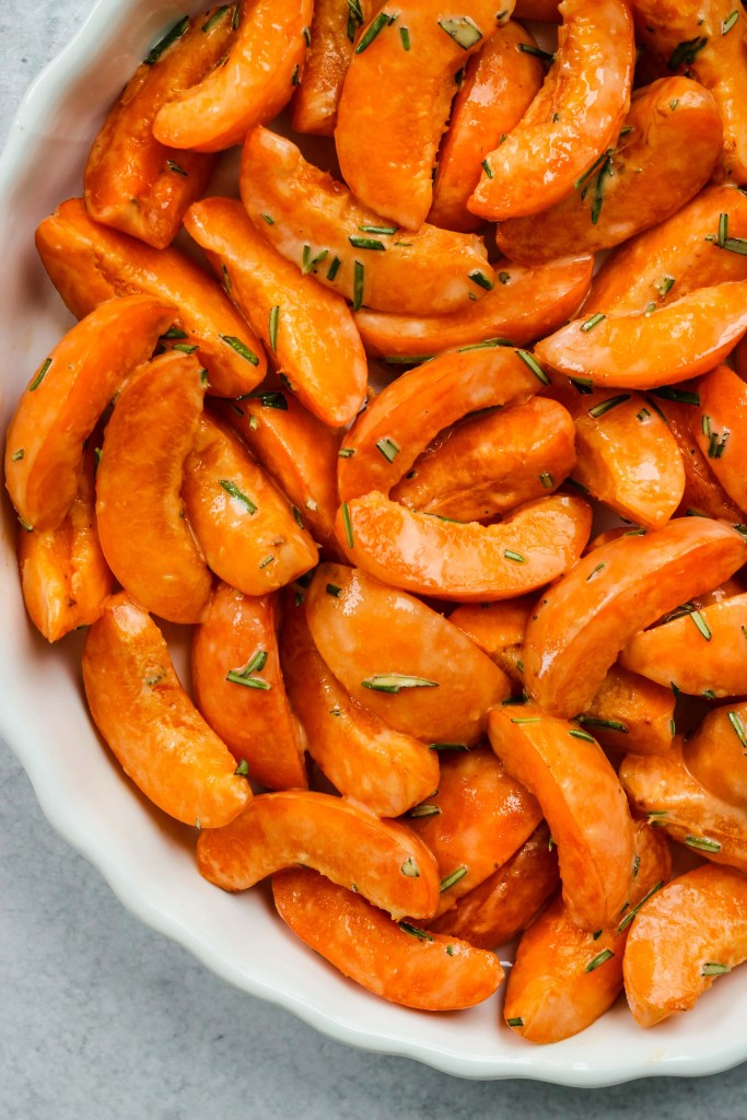 close up sliced apricots and rosemary in white baking dish