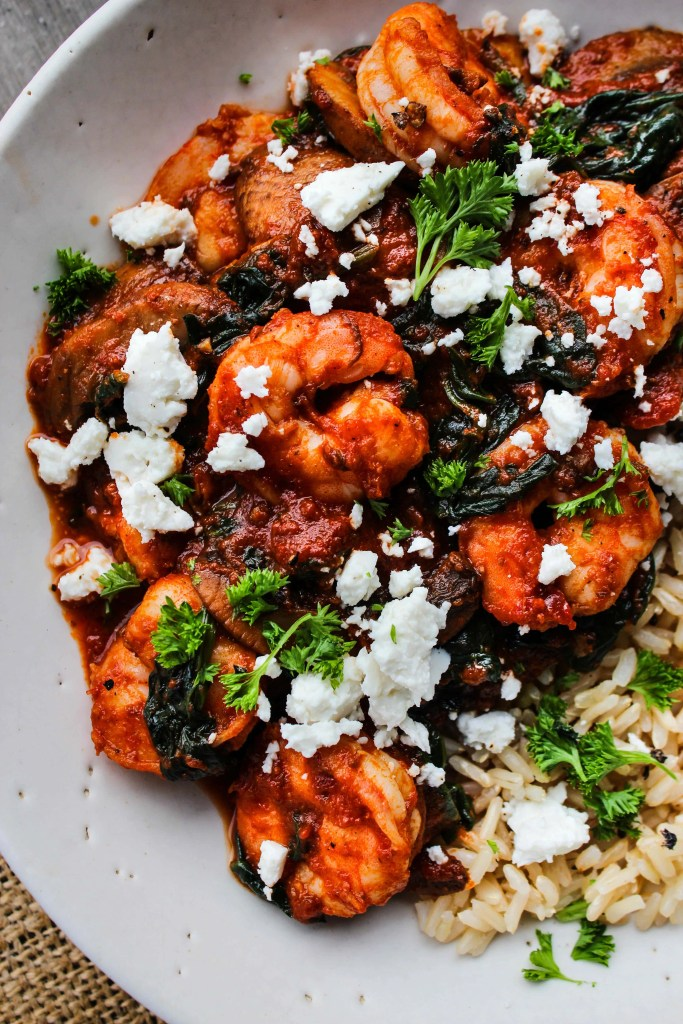 close up of white bowl with sauteed shrimp, tomato sauce,vegetables, feta, parsley