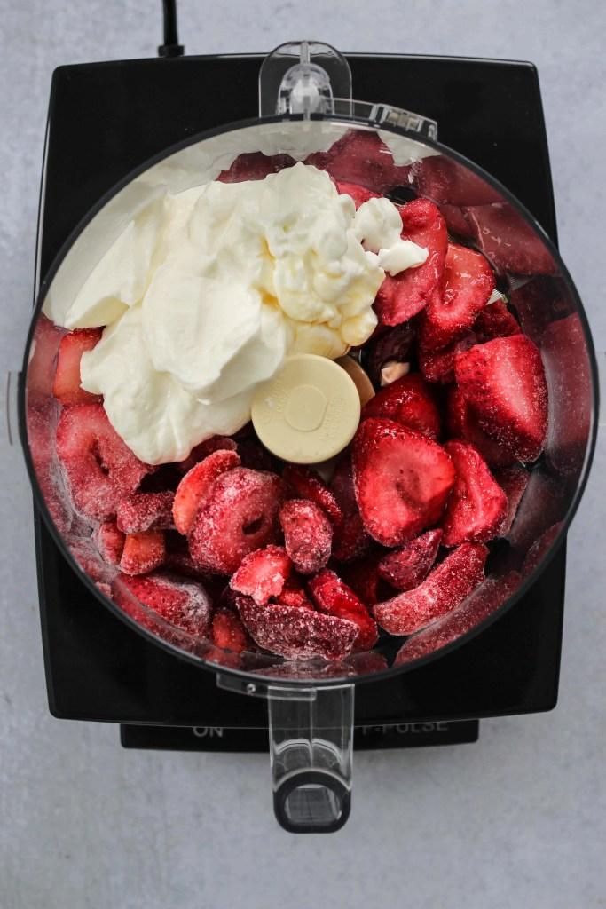 overhead shot of food processor with frozen strawberries and greek yogurt