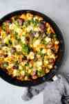 overhead shot of black skillet with a root vegetable frittata, goat cheese, and parsley inside