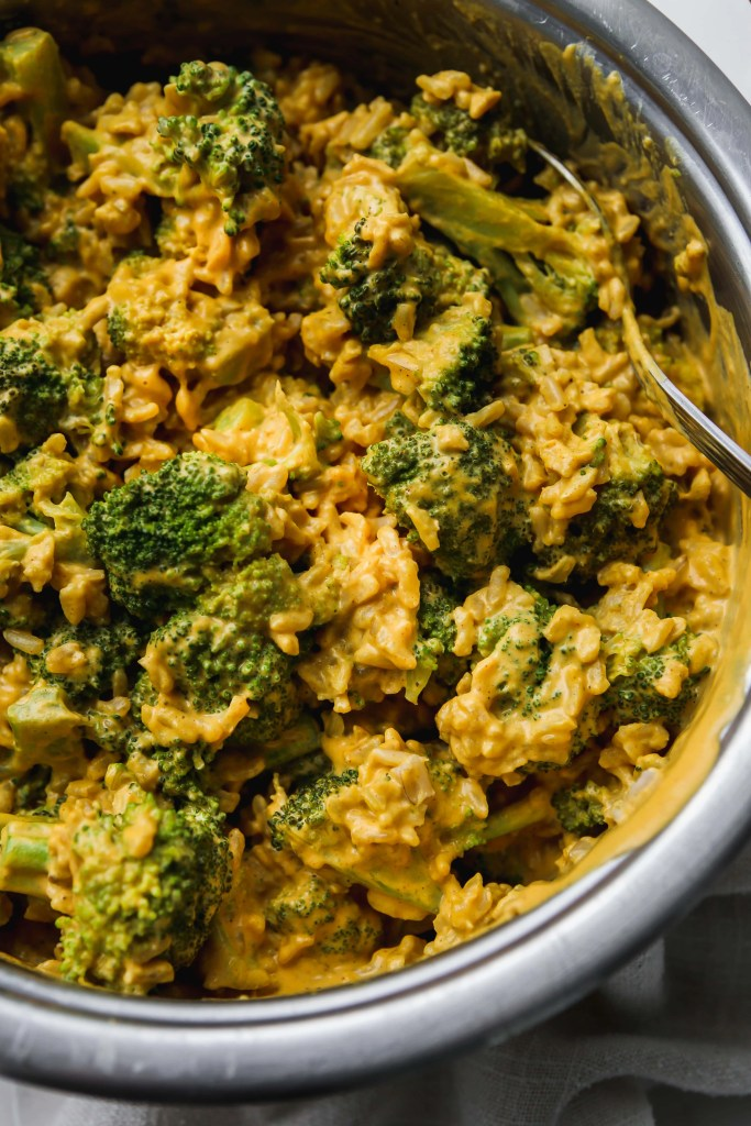 closeup photo of pot filled with vegan cheesy broccoli rice
