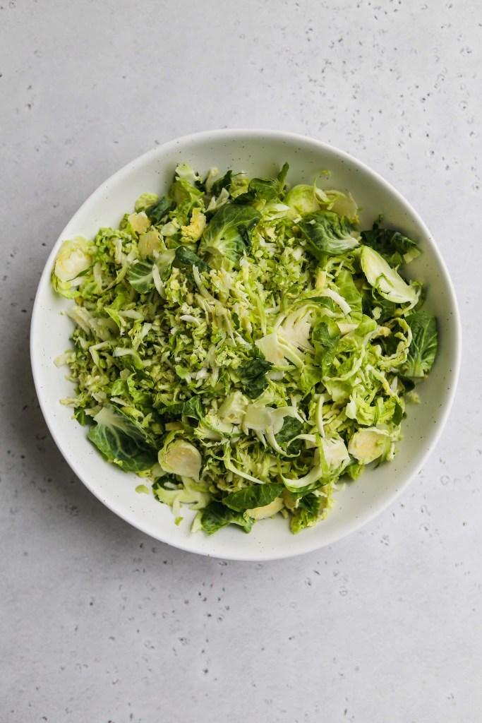 overhead photo of white bowl with shredded brussels sprouts inside