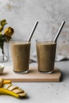 straight on shot of two glasses of chai tea smoothie with straws on a wooden cutting board
