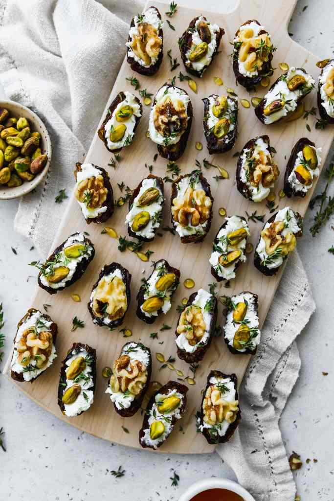 overhead photo of wood cutting board with 25 date halves stuffed with goat cheese and topped with walnuts, pistachios, honey, and thyme
