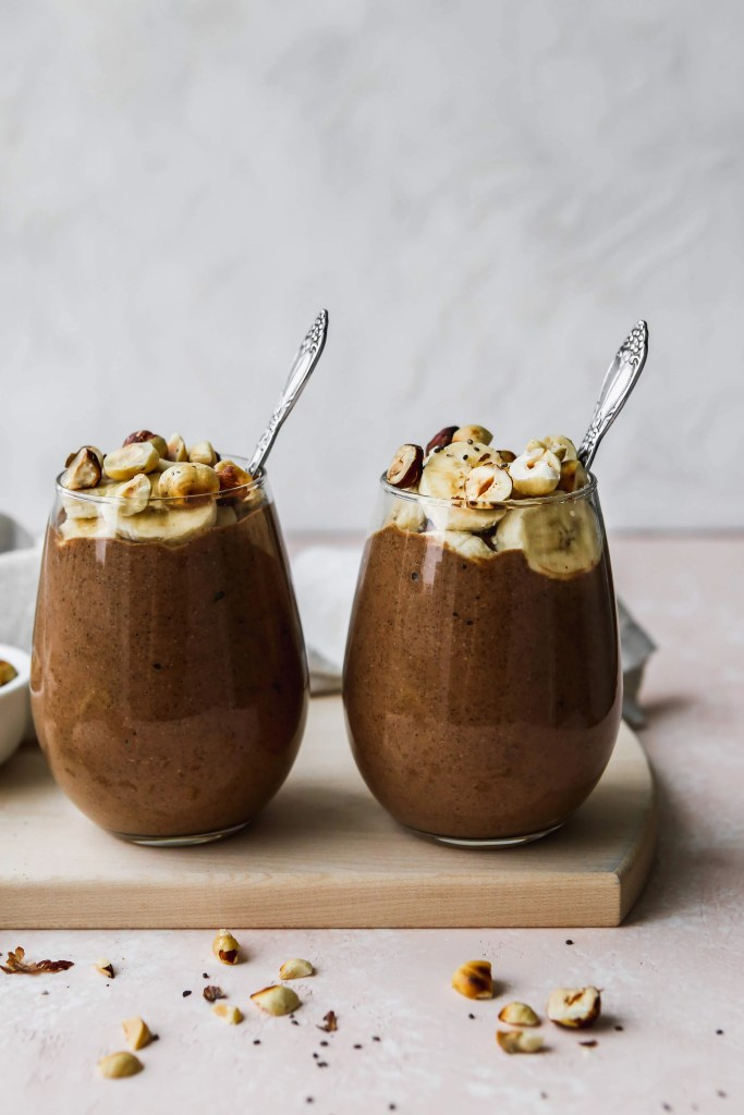straight on shot of two small glasses of chocolate banana chia pudding topped with banana slices and hazelnuts on a wood cutting board