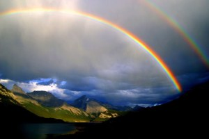 A photograph of a double rainbow, highlighted by puffy white clouds against a blue sky. The foreground is dark, and the background has green grass and two mountains.