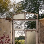 Countryside view through derelict wall and window