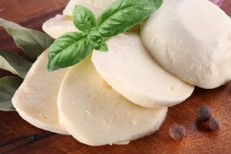 sliced buffalo mozzarella on a board with a sprig of basil. Learn all about what makes this cheese so delicious!