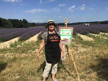 Woman in front of an easel and lavender fields during Walk the Arts art workshops in Provence France