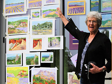 Artist in front of her paintings done during our art holidays in France