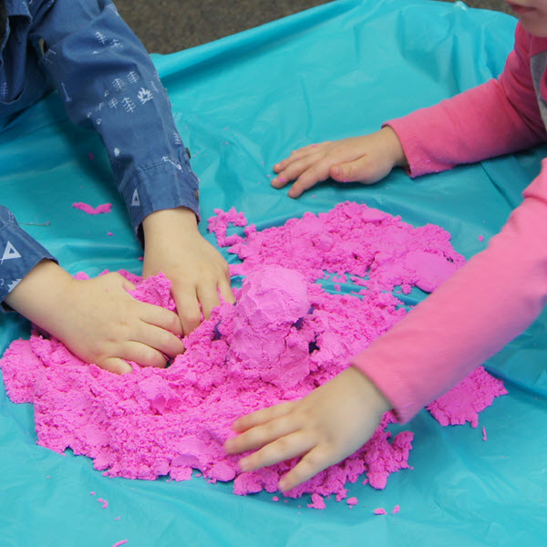 Two small children play with pink sand on a colorful table.