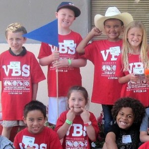 A group of children in red VBS shirts smile.