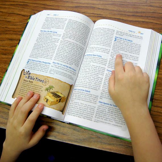 A child's hands on an open bible.