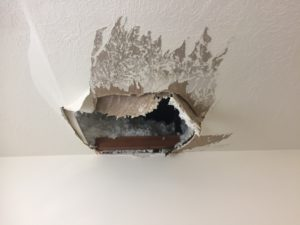 hole in white ceiling that needs repairing