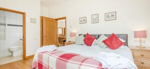 Teal Cottage bedroom with raspberry colours 3 bedrooms sleeps 6 people in beautiful en suite bedrooms at Wallops Wood Cottages