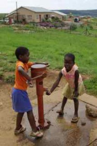 Ufafa children play at the water pump near the Woza Moya offices.