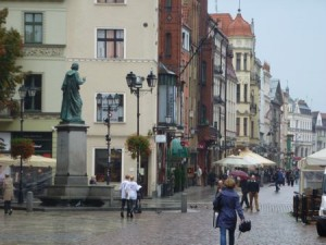 Nicolaus Copernicus surveys his birthplace, Toruń.