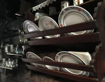 Altes Geschirr auf einem noch älteren Regal im Inneren der Karseggalm.