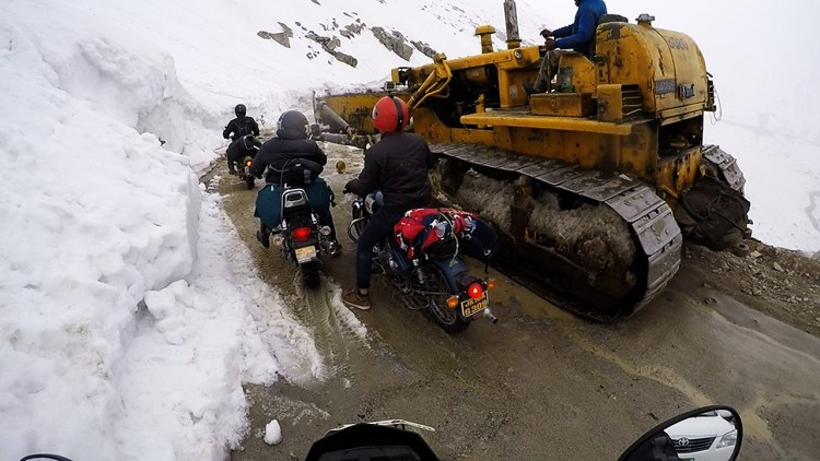 A road roller clearing snow in a mountain road
