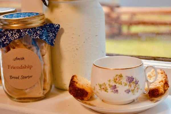 amish friendship bread starter in mason jar and loaf sitting on a teacup on the window sill