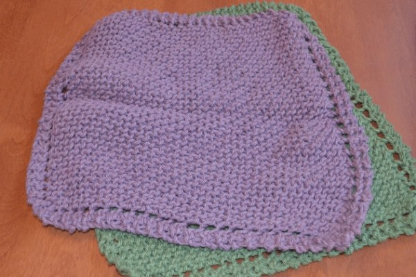 purple and green knitted dishcloths laying on table together both down in the Omas Knitted dishcloth Pattern from Wandering Hoof Ranch