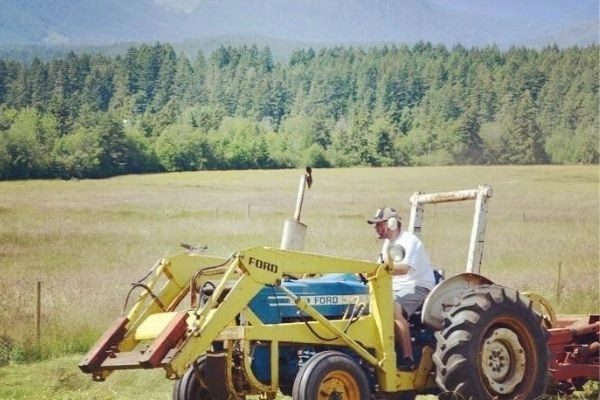 farmer on old tractor cutting hay