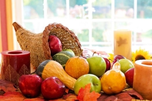 cornucopia of fall harvest on table by window