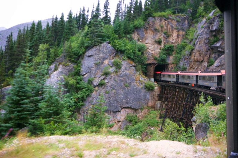 Whitepass and Yukon Railway train cars going into a tunnel in the Rocky Mountains.
