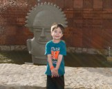 A young boy stands proudly in front of a sculpture - Legend of El Dorado in Colombia