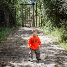 A toddler in an orange shirt smiles and walks towards the camera in the jungle - Legend of El Dorado in Colombia