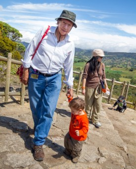 An older man wearing a hat walks with a toddler on an overlook at the lost city of gold in Guatavita Colombia with kids