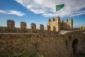 An old castle wall with a Moorish flag flying in Sintra, Portugal