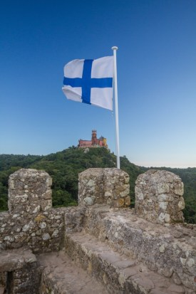 Finnish flag against a blue sky raised from a stone rampart with a colourful castle in the background - Sintra, Portugal