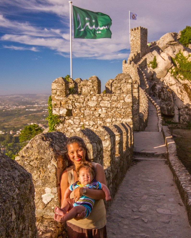 woman and baby smile while walking along the stone ramparts of an ancient castle - Sintra, Portugal