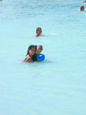 An asian woman and a toddler smile from the blue waters of a lagoon - Iceland's Golden Circle