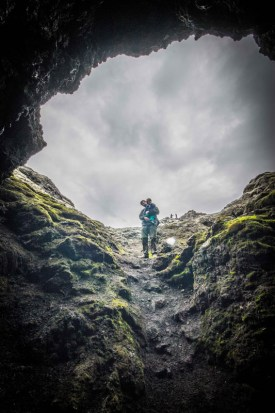 a mother and son are dwarfed by a cave entrance